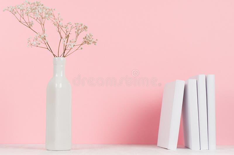 Små torkade blommor i elegant vas och vita böcker på den wood tabellen och mjuk bakgrund för pastellfärgade rosa färger, kopierin royaltyfri foto