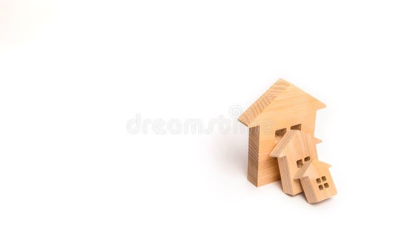 Små trähus faller på det stora huset som en dominobricka Begreppet av köpandefastigheten Försäkring och investeringrisk Fallande  royaltyfria bilder