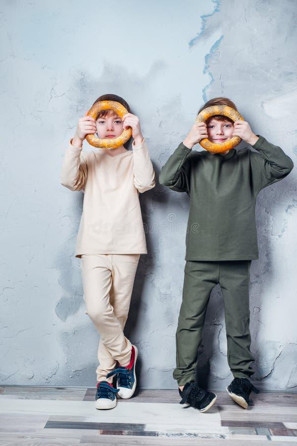 Små tvilling- pojkar som spelar och drömmer av att bli en astronaut Stående av roliga ungar med baglar på den gråa väggen royaltyfri fotografi