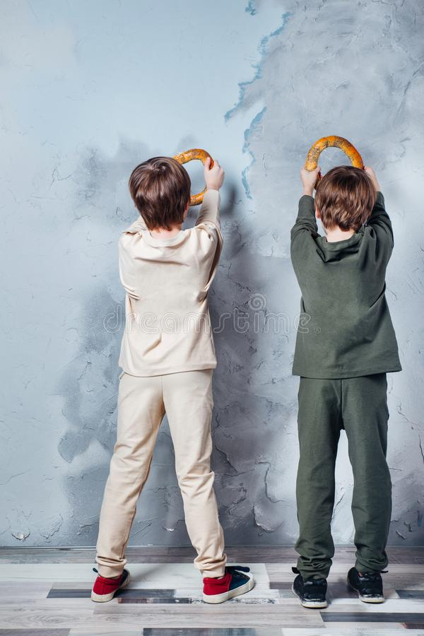 Små tvilling- pojkar som spelar och drömmer av att bli en astronaut Stående av roliga ungar med baglar på den gråa väggen arkivfoto