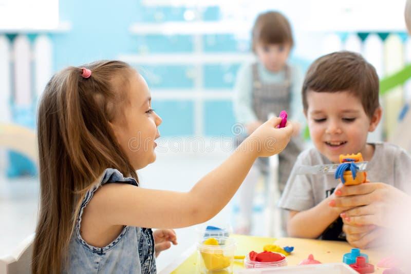 Små ungar har en gyckel samman med färgrik modellera lera på daycare Idérika ungar som gjuter i dagis Barn arkivbild