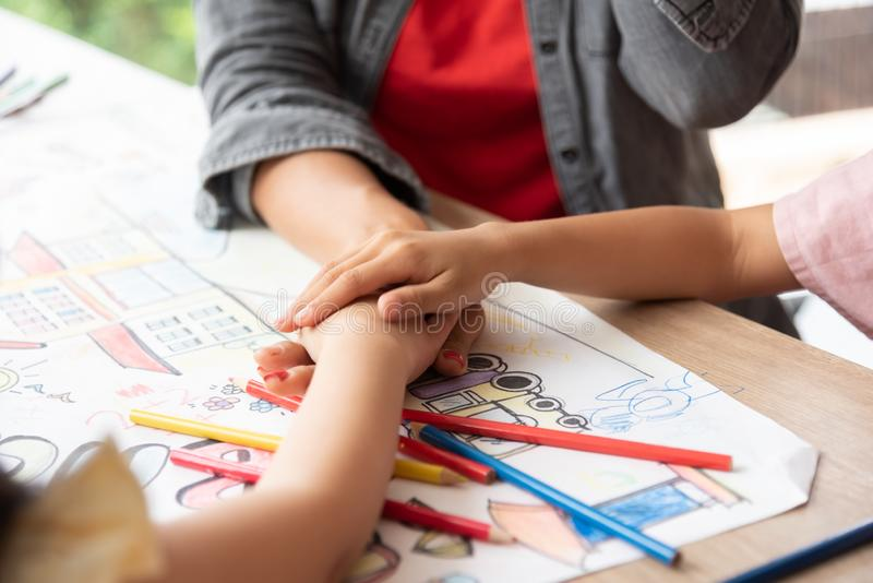 Små ungar och lärare som tillsammans sätter deras händer royaltyfria foton