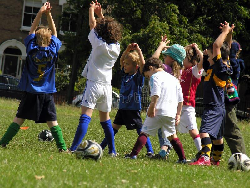 Små ungar på fotbollutbildning i parkera arkivfoton