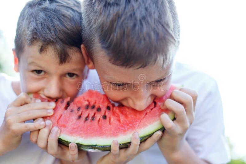 Små ungar som äter den utomhus- vattenmelon arkivfoto