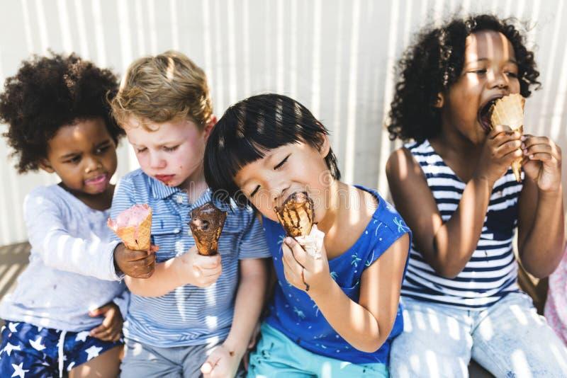 Små ungar som äter smaskig glass royaltyfri bild