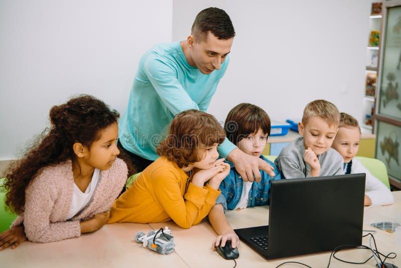 små ungar som arbetar med läraren royaltyfria foton