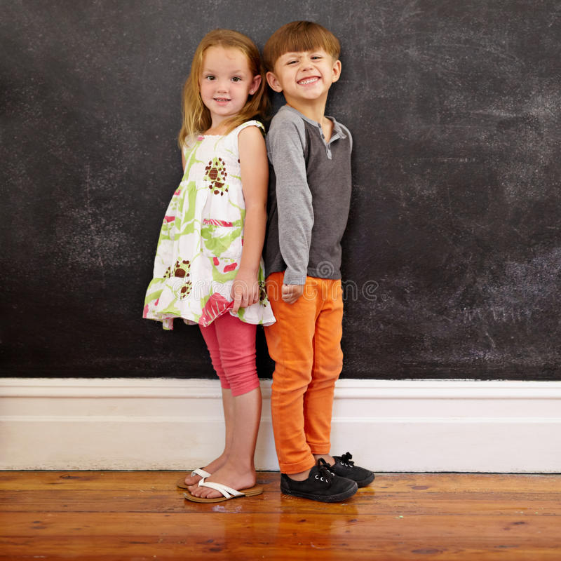 Små ungar som framme står av svart tavla royaltyfria foton