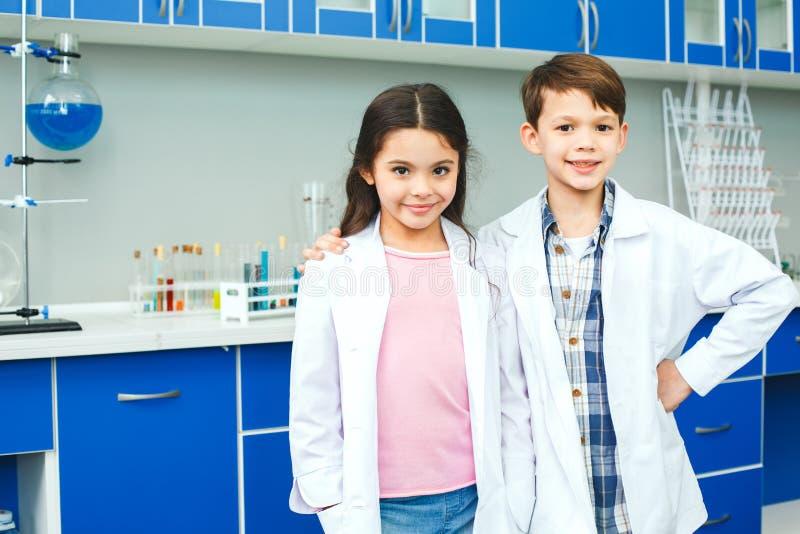 Små ungar som lär kemi i skolalaboratoriumbästa vän royaltyfri bild