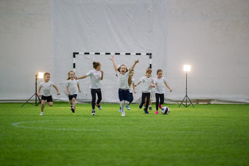 Små ungar som spelar fotboll inomhus Barnfotbollslagspring på fältet arkivbild