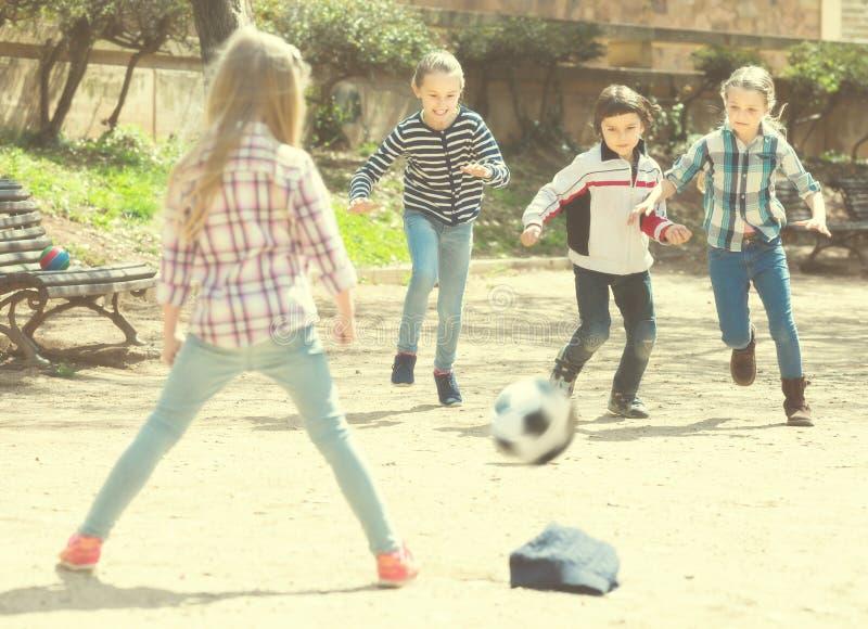 Små ungar som spelar gatafotboll utomhus royaltyfri foto