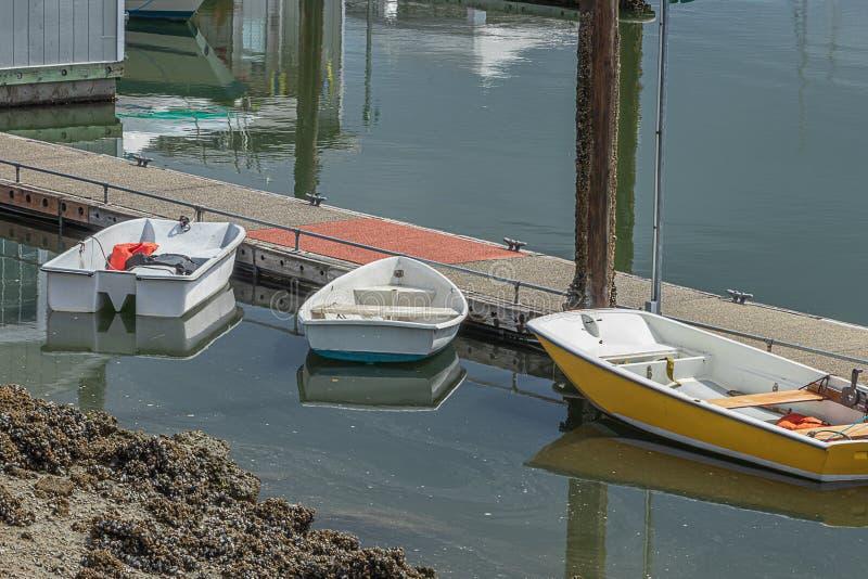 Små uthyrnings- fartyg som anslutas längs trägångbanan ut på vatten arkivfoto