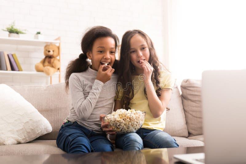 Små vänner som håller ögonen på tecknade filmen och äter popcorn arkivfoton