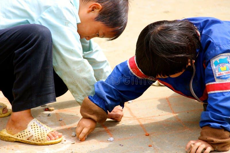 Små vietnamesiska pojkar som spelar på banan royaltyfria foton