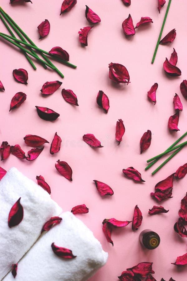 Små vita handdukar och magentafärgat potpurri på rosa bakgrund royaltyfria bilder