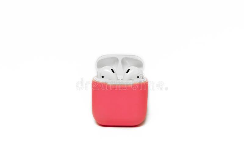 Små vita trådlösa hörlurar med uppladdareasken i ljus rosa räkningsask royaltyfri foto