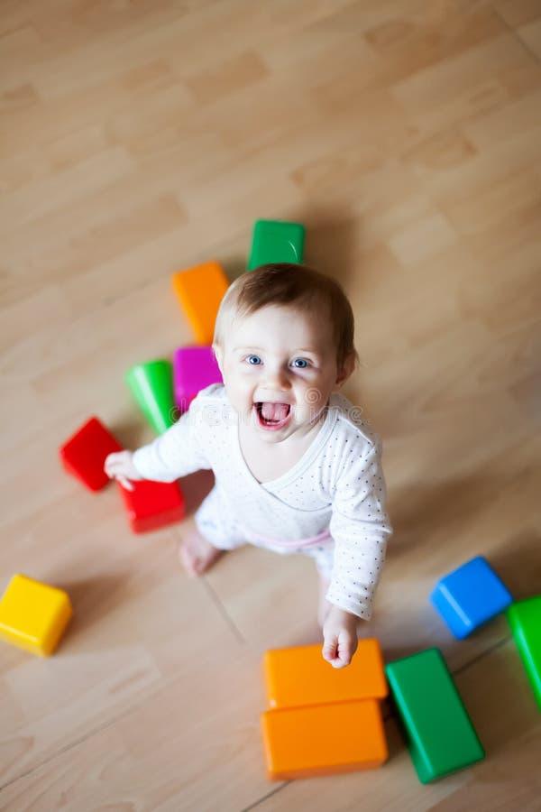 Småbarn av 9 månader som spelar på golv av huset arkivfoto