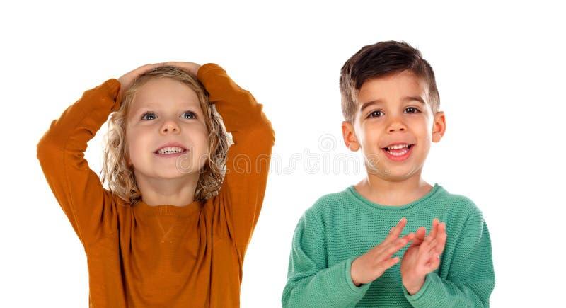 Småbarn som täcker hans huvud, och annan som aplauding royaltyfria foton