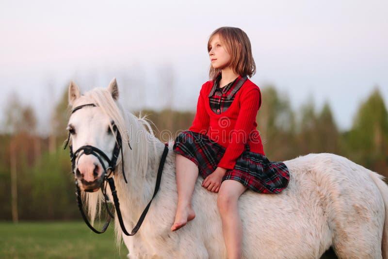 Småbarnet sitter i den tänkta vita ponnyn och ser upp arkivbild