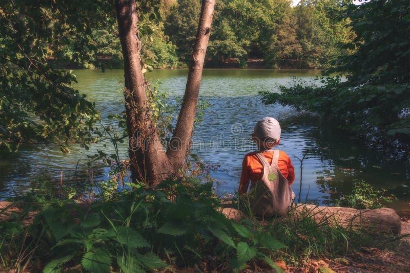 Småbarnet sitter i skogen nära dammet och tycker om den härliga naturen royaltyfria foton