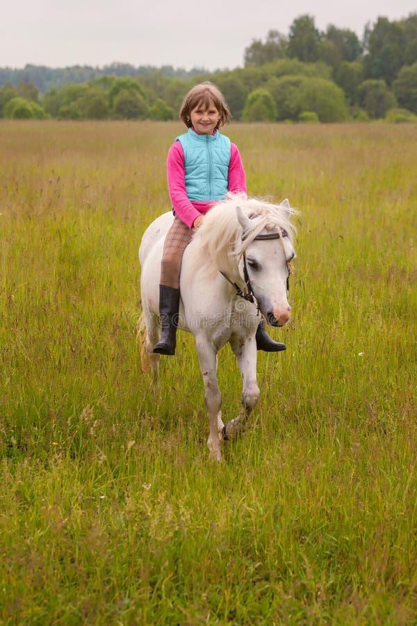 Småbarnridning på en vit häst och le utomhus fotografering för bildbyråer