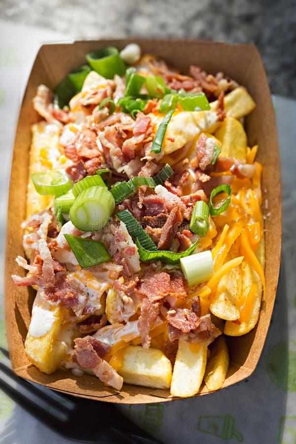 Småfiskar med cheddarost, frasig bacon, vitlöksås & vårlöken fotografering för bildbyråer