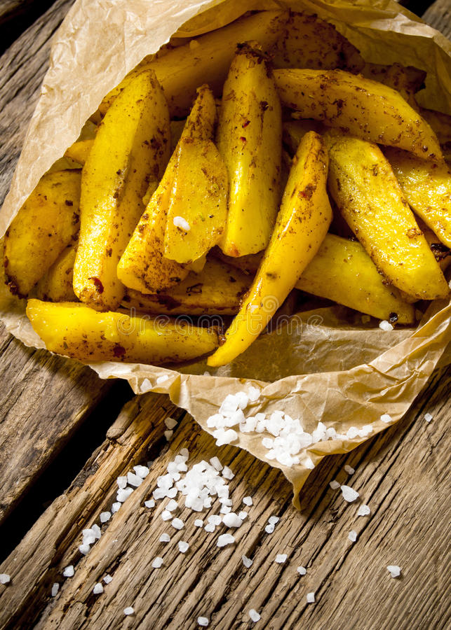Småfiskar med kryddor och saltar på träbakgrund arkivfoton