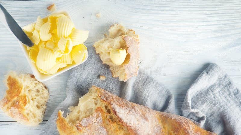 Smör och nytt frasigt hemlagat bröd Sund organisk frukost på den lantliga vita trätabellen royaltyfria bilder