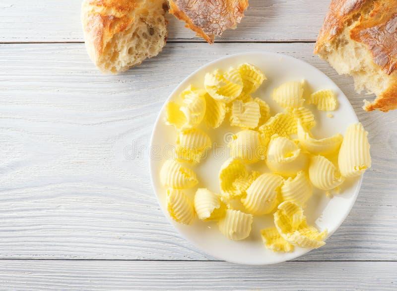 Smör och nytt frasigt hemlagat bröd Sund organisk frukost på den lantliga vita trätabellen royaltyfri foto