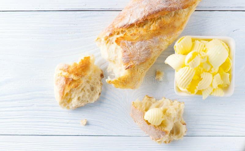 Smör och nytt frasigt hemlagat bröd Sund organisk frukost på den lantliga vita trätabellen arkivfoto