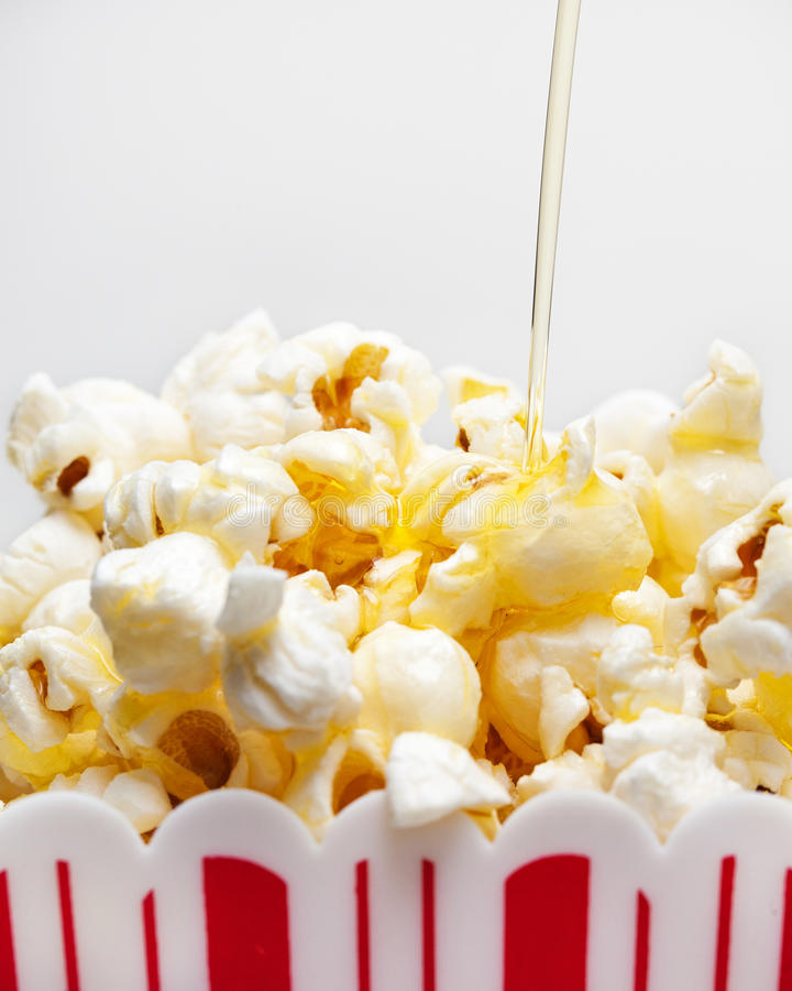 Smör som duggar över popcorn royaltyfri bild