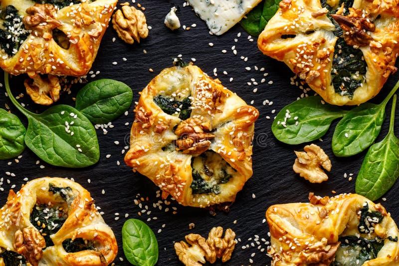 Smördeg som är välfylld med spenat och Gorgonzola ost på en mörk bakgrund royaltyfri fotografi