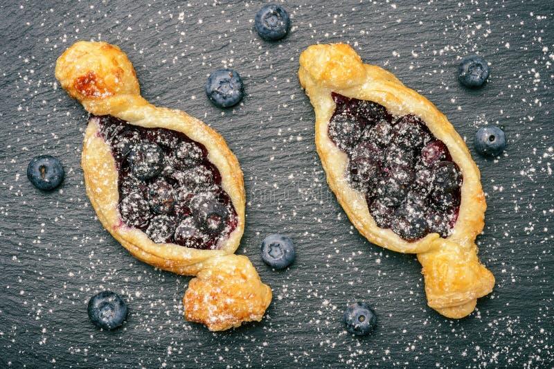 Smördegar med blåbär på svart bakgrund arkivfoto