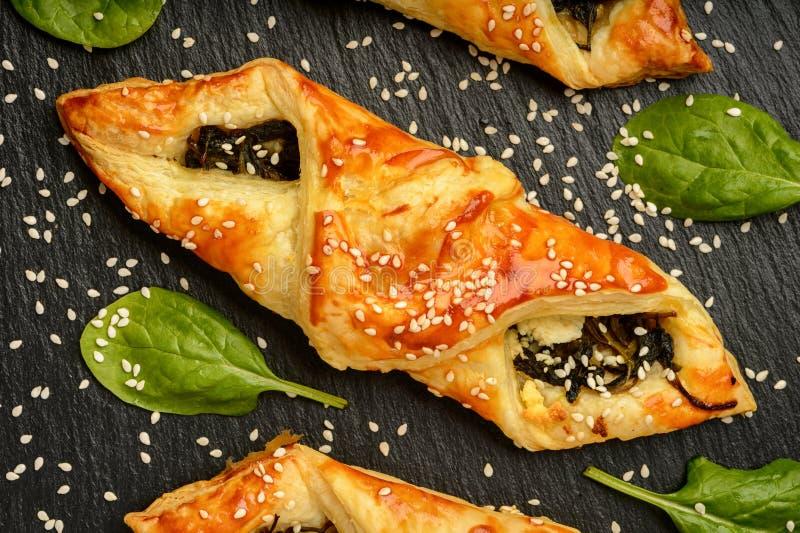 Smördegar med spenat-, ost- och sesamfrö på svart bakgrund arkivfoto