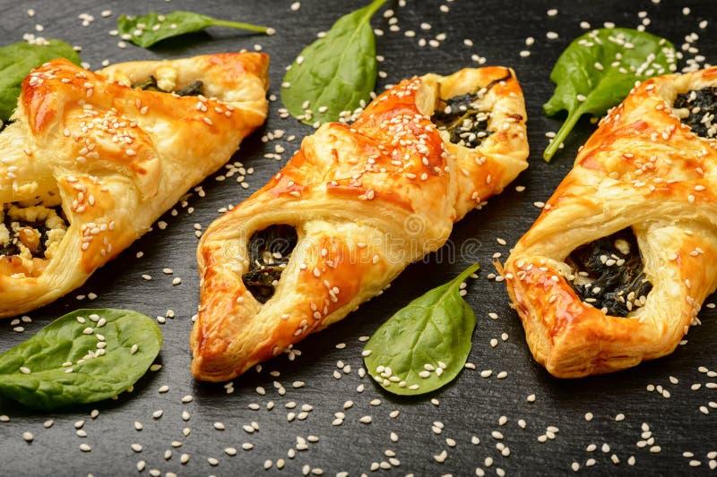 Smördegar med spenat-, ost- och sesamfrö på svart bakgrund arkivfoton