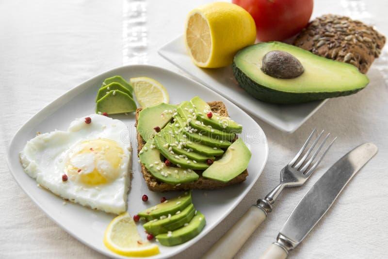 smörgås; avokadosmörgås; ägg; citron; sesam; bröd; gaffel; kniv royaltyfri fotografi