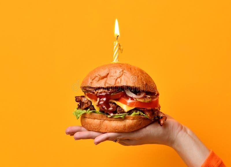 Smörgås för grillfest för hamburgare för kvinnahandhåll stor med nötkött och den tända stearinljuset för födelsedagparti på gulin royaltyfria bilder