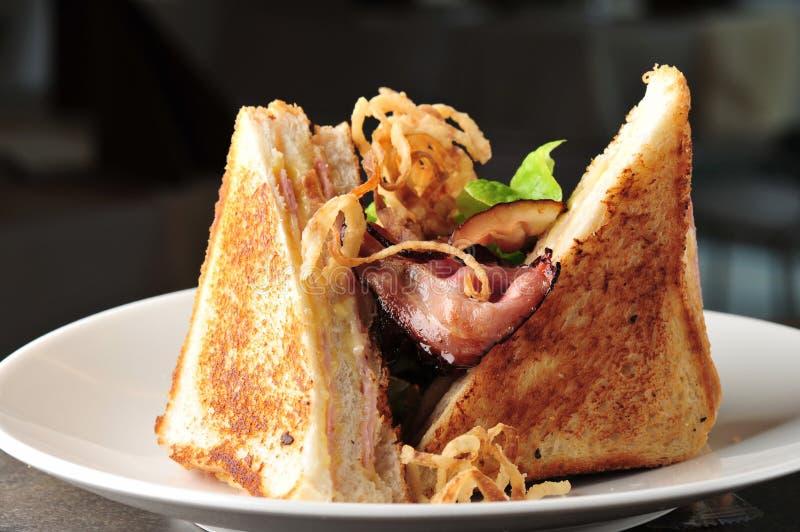 Smörgås för klubba två med bakad bacon royaltyfri foto