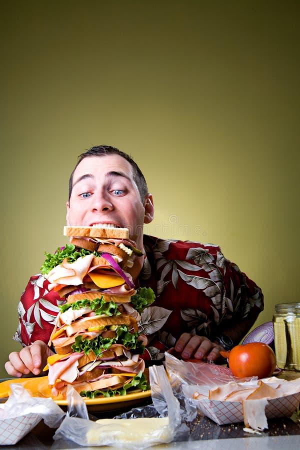 Smörgås: Mannen lutar över för att äta den jätteDagwood smörgåsen arkivfoto