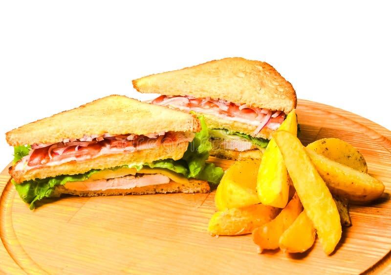 Smörgås med bakade potatisar på ett träbräde som isoleras på vit arkivfoton