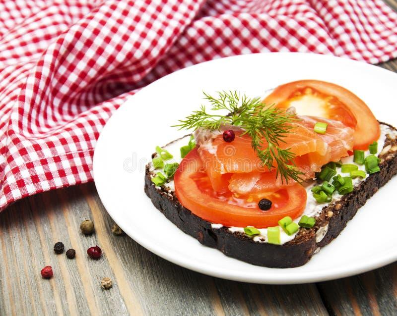 Smörgås med den rökte laxen och tomaten arkivbilder