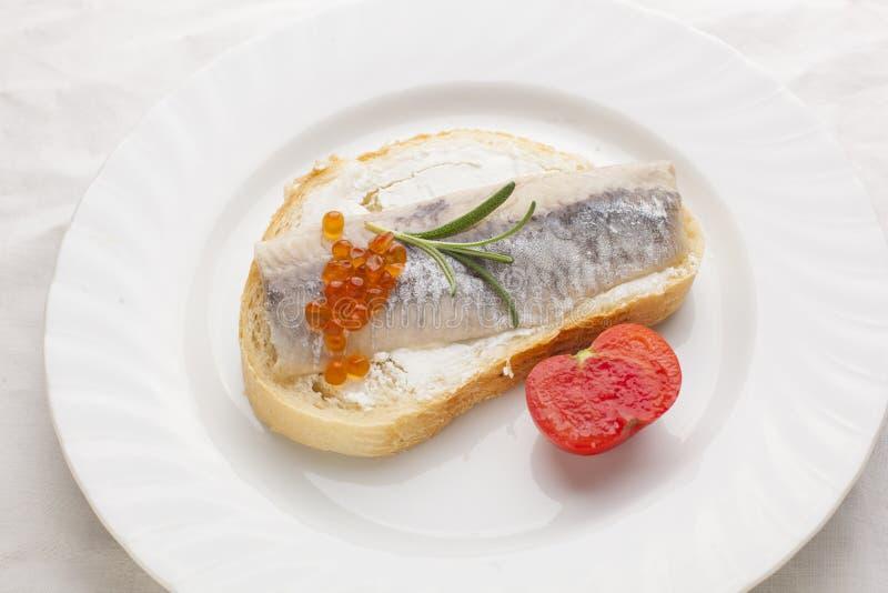 Smörgås med den sillfisken och kaviaren på bröd, körsbärsröd tomat royaltyfri bild