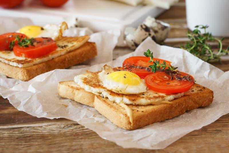 Smörgås med det stekte ägget, tomaten och stekt ost arkivfoto