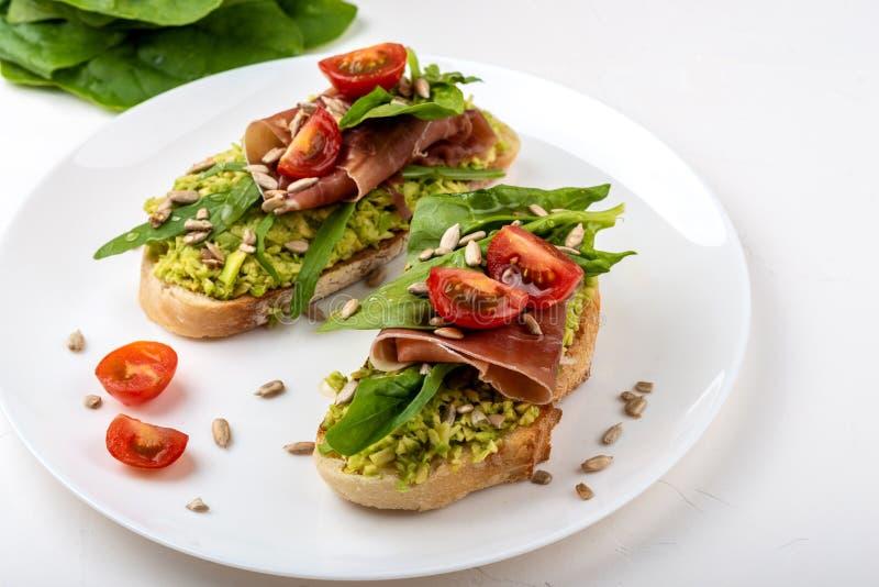 Smörgås med prosciuttoen, jamon, tomater och avokadot på vit bakgrund arkivbilder