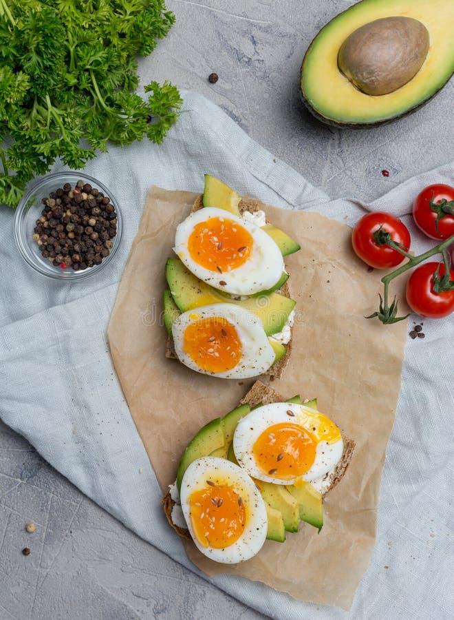 Smörgås på kornbröd med det kokta ägget och avokadot royaltyfria bilder