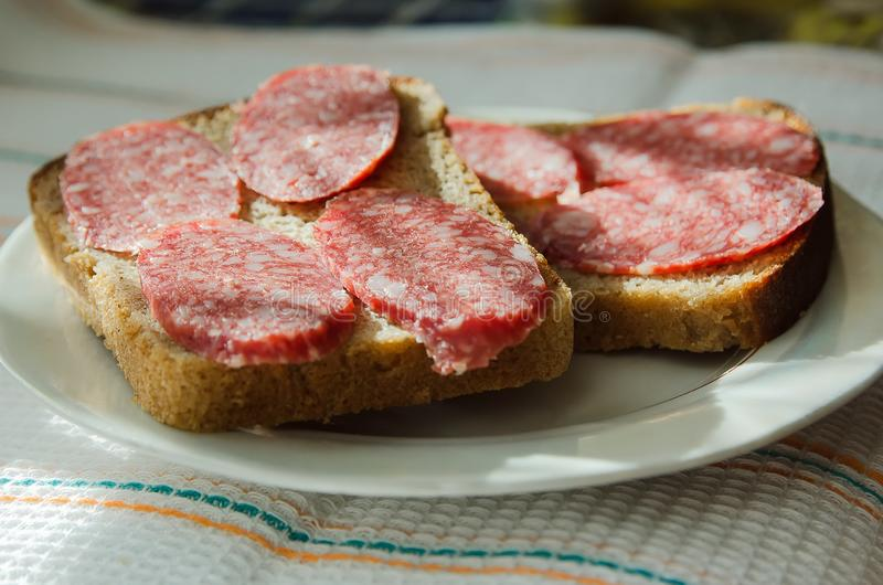 Smörgåsar av svart bröd med rökte korvlögner på en platta arkivfoto