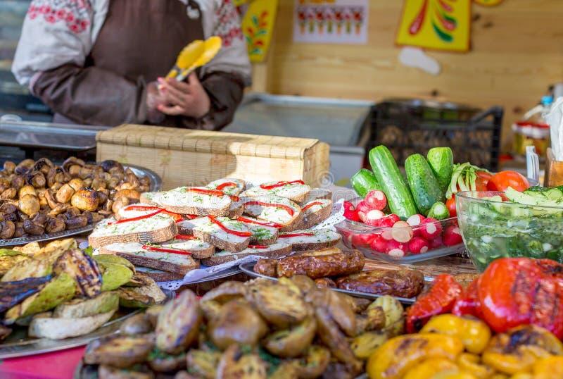 Smörgåsar, grönsaker, champinjoner och annan mat på gatamatfestivalen arkivfoto