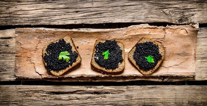 Smörgåsar med den svarta kaviaren och gräsplaner arkivfoto