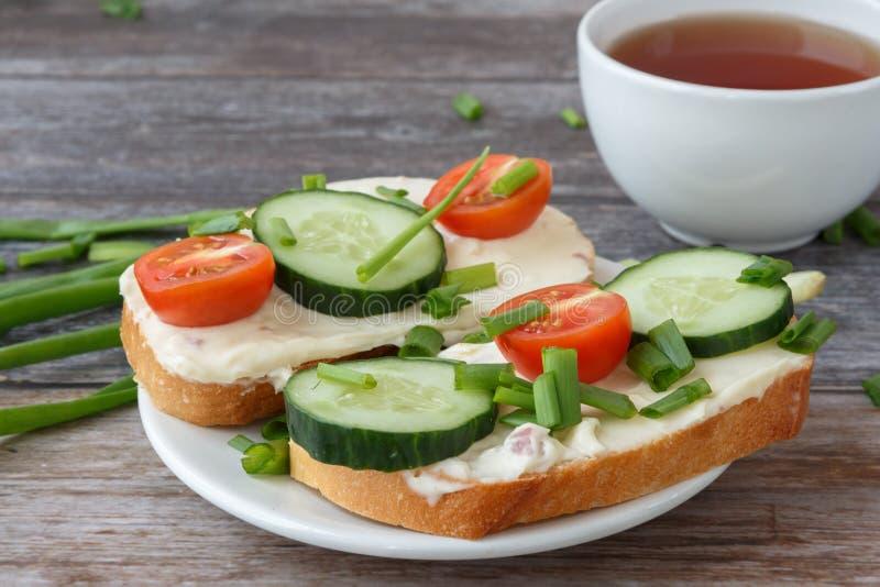 Smörgåsar med gräddost, körsbärsröda tomater, gurkor och salladslökar fotografering för bildbyråer