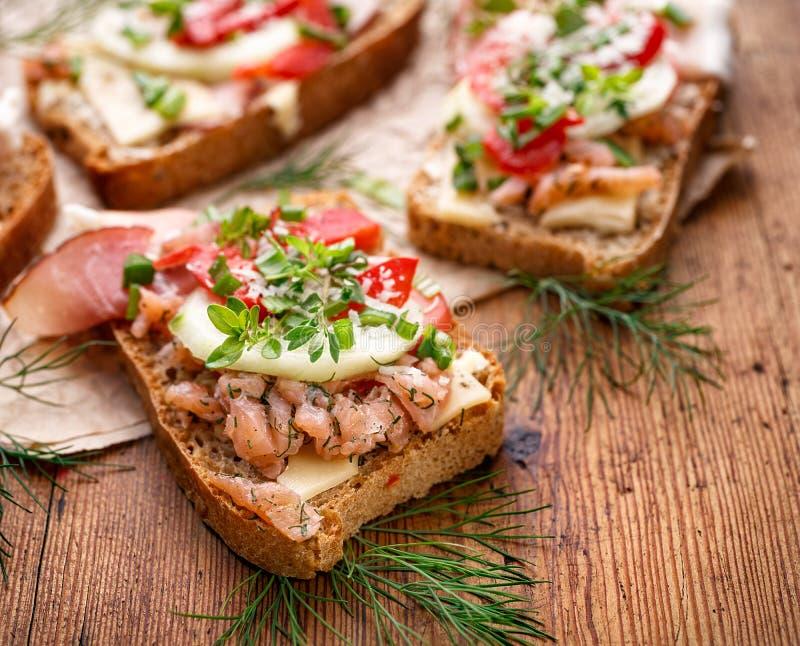 Smörgåsar med hemlagat bröd som innehåller fisken, grönsaker och nya örter arkivfoto