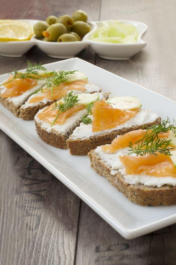 Smörgåsar med laxen, ricotta, dill och gurkan royaltyfri fotografi